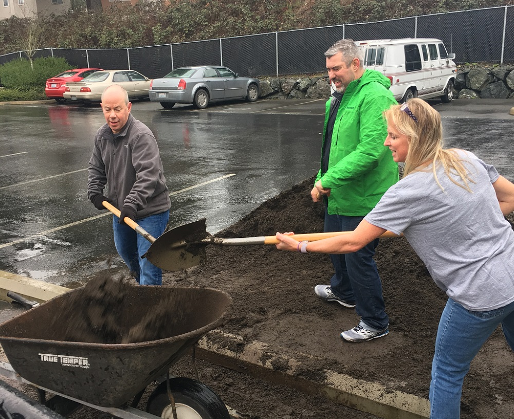 Susan's Youth Center volunteers shovel dirt outside